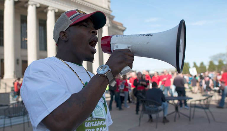 African American Male On A Bullhorn In Front Of A Congress Building
