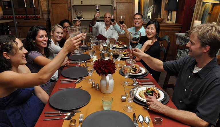 Group Of People Making A Toast At The Dinner Table