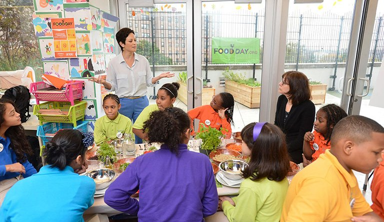 Instructor Discussing Healthy Foods With Kids In Classroom