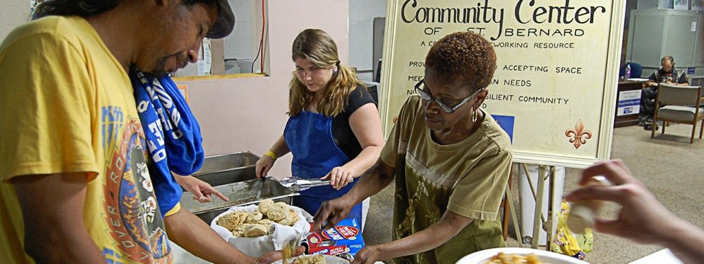 Woman Handing Out Food At A Community Center