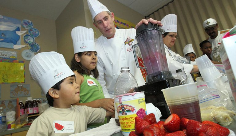 Kids Using Blender Alongside A Chef