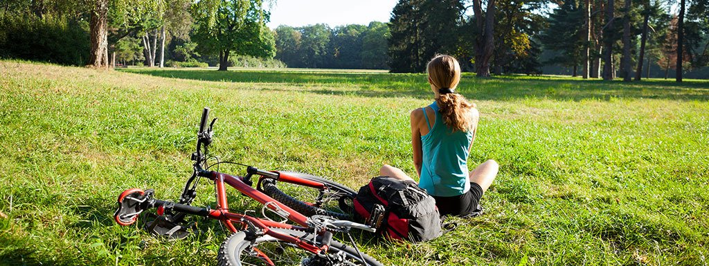 Woman Sitting With Her Bike In The Park