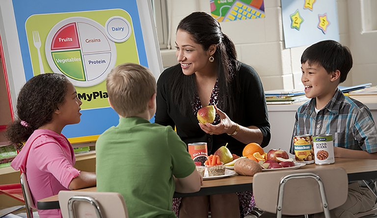 Teacher Eating Fruits & Vegetables In A Classroom With Students