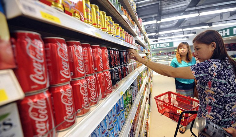 Woman Picking Up Soda Inside Of A Supermarket