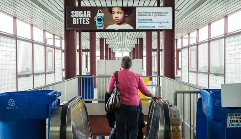 Women Going Down An Escalator Under An Anti-Sugar Campaign Poster