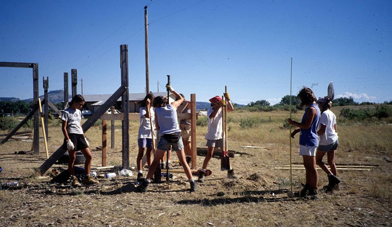 Students Digging Holes In A Field