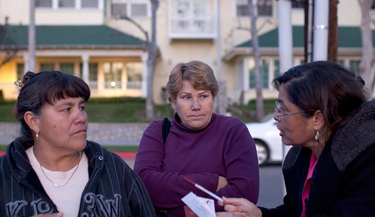 Latino Women Having A Discussion On A Residential Block
