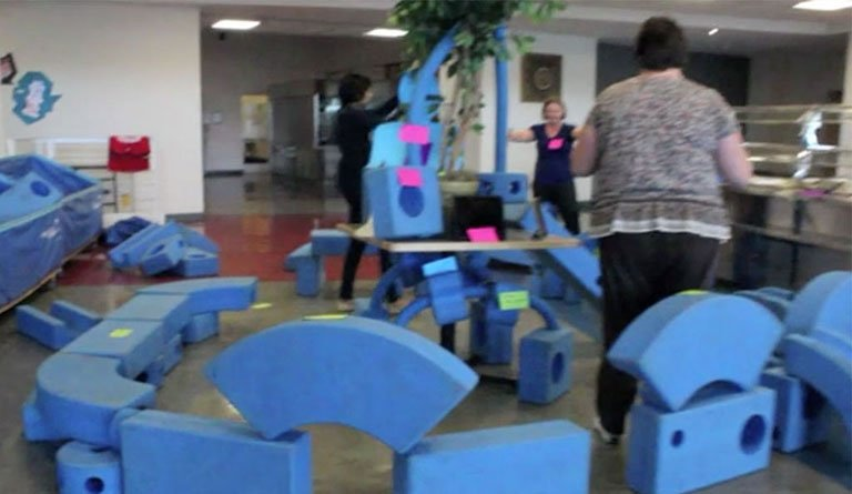 Women Standing In Cafeteria With Foam Blocks