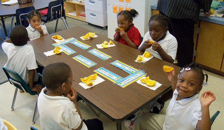 Kids Eating Snacks On A Table In A Classroom