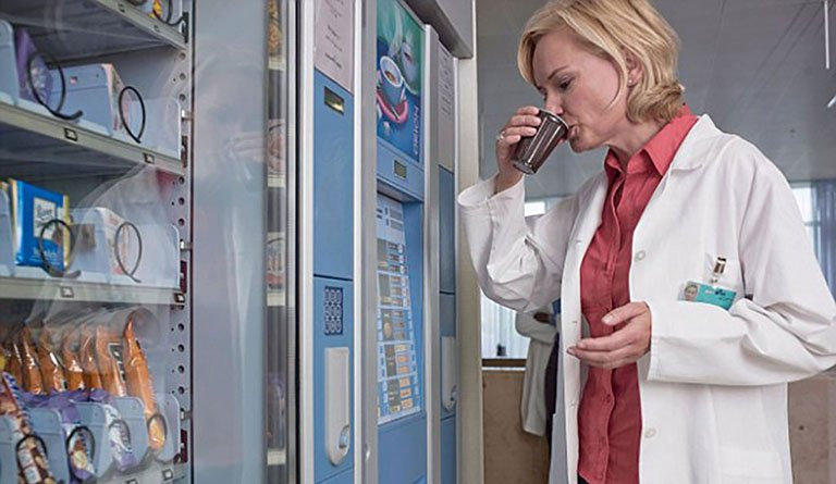 Hospital Personnel Drinking Soda From Vending Machine