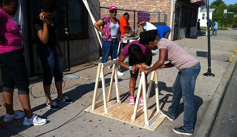 Students Working To Assemble A Wooden Structure Outside