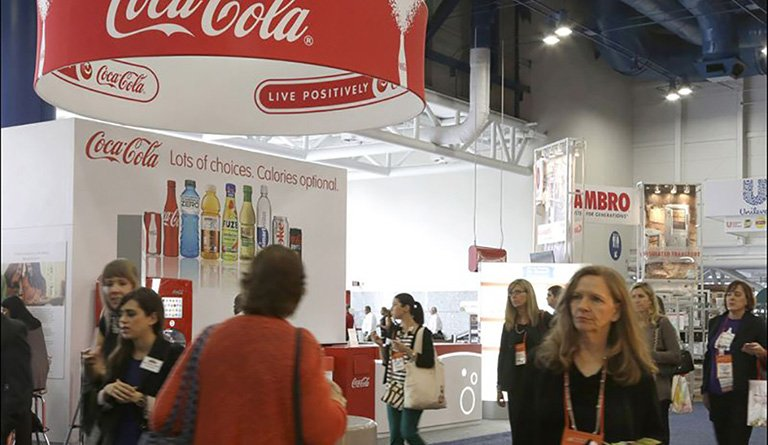 Patrons Walking By A Coca-Cola Kiosk At A Conference