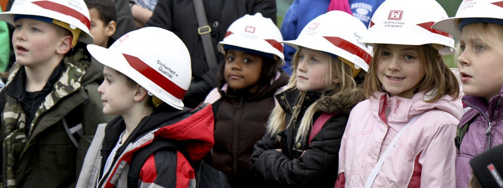 Kids In Hard Hats In A Field